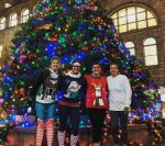 4 women water polo players in holiday sweaters in Pittsburgh in front of Christmas tree